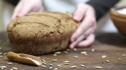 Baker putting freshly baked organic sourdough rye bread down