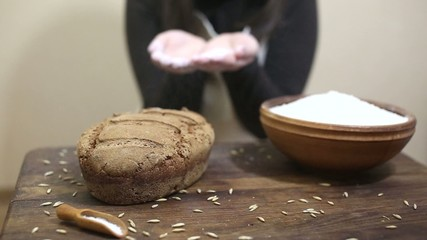 Baker blowing flour on freshly baked sourdough rye bread