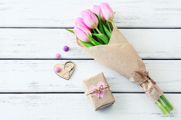 Beautiful pink tulips in paper with present box