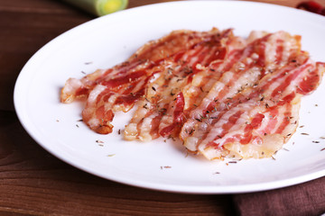 Strips of bacon in white plate with spices and chili pepper