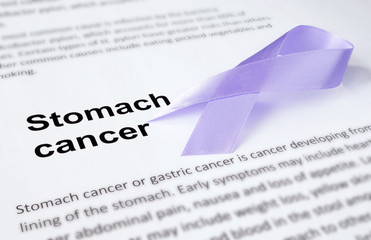 Paper with stomach cancer and periwinkle blue ribbon.