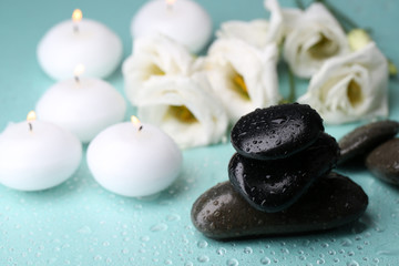 Spa stones with candles and flowers on blue background close-up