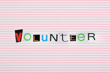 Inscription volunteer on colorful background