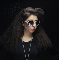 brunette wearing sunglasses posing in the studio