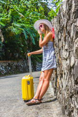 Girl with a yellow suitcase on a resort