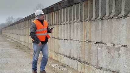 Engineer with tablet PC walking near the concrete wall