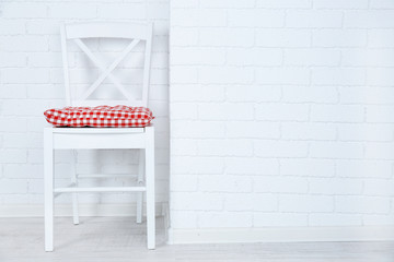 Wooden chair with pillow on white brick wall background
