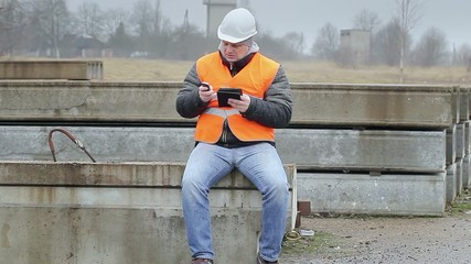 Engineer with cell phone and tablet PC on the concrete panels
