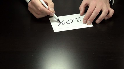 Hands writing the 20 percent