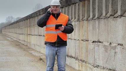 Engineer talking on cell phone the concrete wall