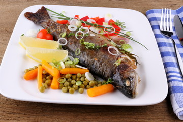 Grilled trout with quite different vegetables with cutlery