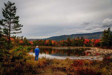 Man at Pond Enjoys Autumn Leaves