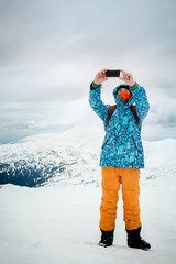 Man taking selfie with smartphone on mountains background