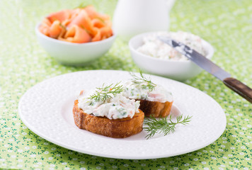 Canape with soft cheese spread on white plate