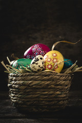 Easter eggs in basket on rustic wooden planks