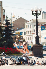 Feeding pigeons. Girl feeds pigeons in square in city