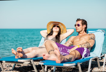 Couple is taking the sun at the beach while relaxing