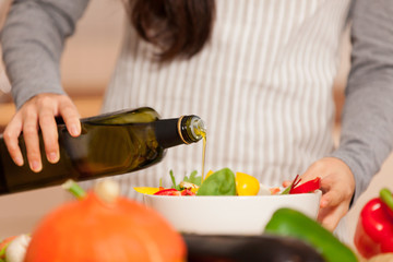 Closeup of woman pouring olive oil into the colorful salad