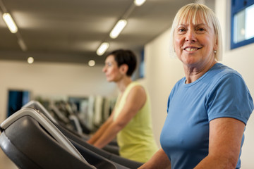 Smiling mature woman is looking towards the camera while running