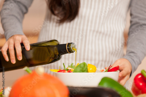 Fotobehang Koken Closeup of woman pouring olive oil into the colorful salad