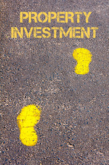 Yellow footsteps on sidewalk towards Property Investment message