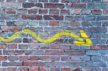 Pfeil in Gelb an einer Mauer