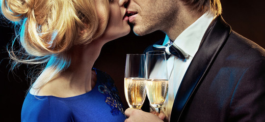Romantic couple kissing and drinking champagne