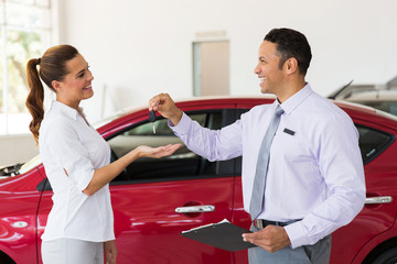 young woman receiving new car key
