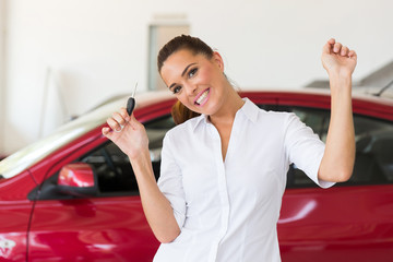 young woman collecting her new car from dealership