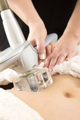 Woman receiving vacuum treatment at body clinic