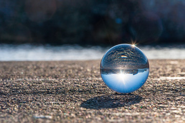 Glass transparent ball on dark background and grainy surface.