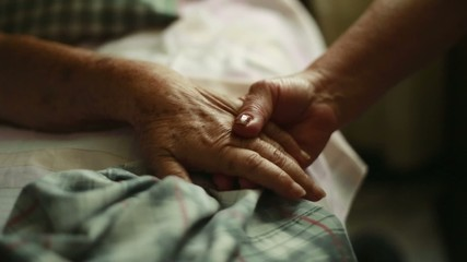 Elderly person holding hands as she lays down in bed