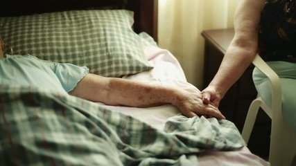 Elderly Woman lying down and holding another woman's hands