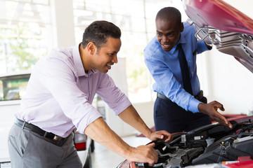 salesman and customer looking at a car engine