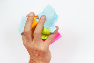 Hand crushes paper trash on a white background