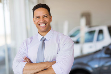 vehicle dealership principal with arms crossed in showroom