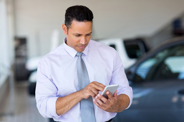 mid age car salesman using cell phone