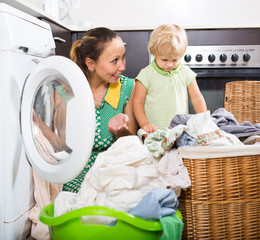 Woman with child near washing machine