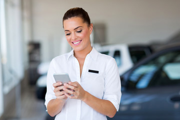 young car sales consultant using smart phone