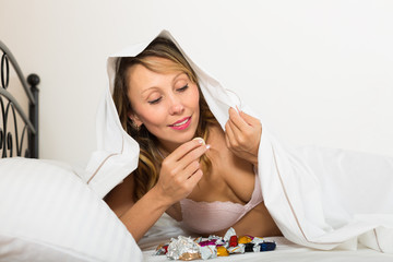 Female eating sweets in bed