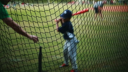 Shot from behind net of a Kid Practicing his Batting