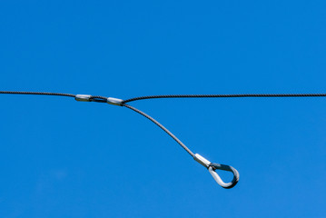 Single thin metal cable loop hanging on sky
