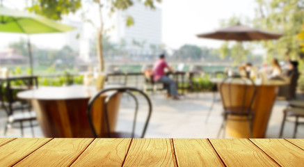 wooden table with blur coffee shop Background