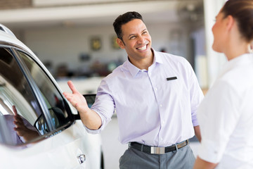 salesman selling car to a customer in showroom