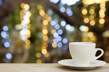 coffee cup on wood table with blur bokeh lights Background