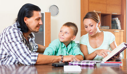 Schoolboy studying with parents
