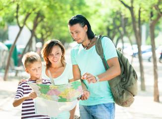 family of three searching way at  map