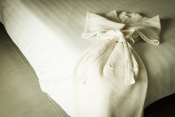 white bathrobe on bed