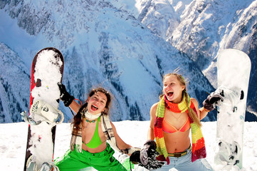 Girls snowboarders in bikinis in the mountains