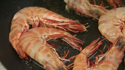 Shrimps being fried in pan then turned over with tongs.